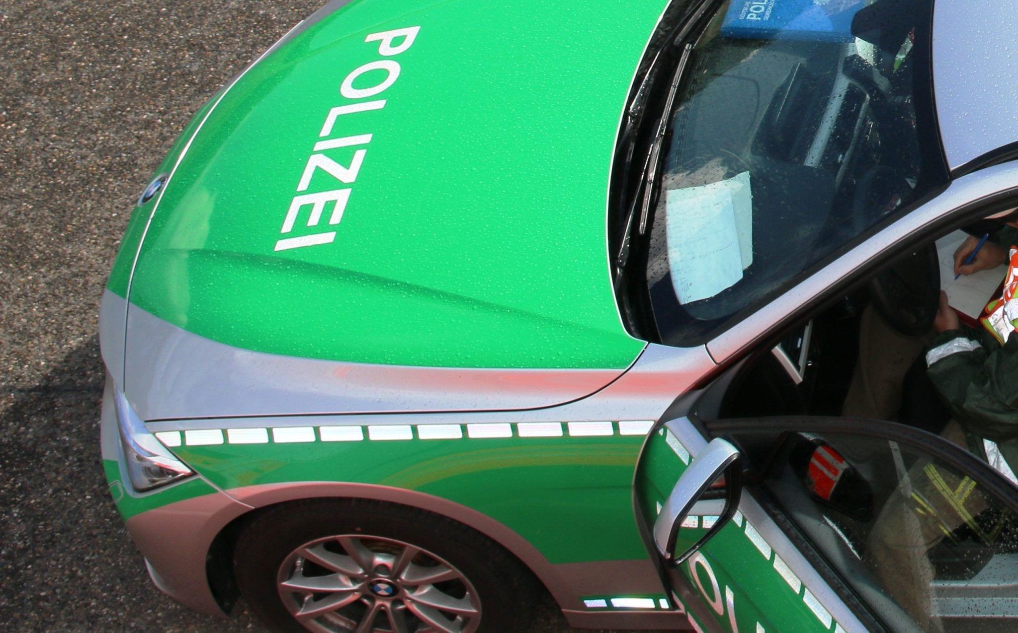 Polizeifahrzeug mit Polizeibeamten im Fahrzeug
