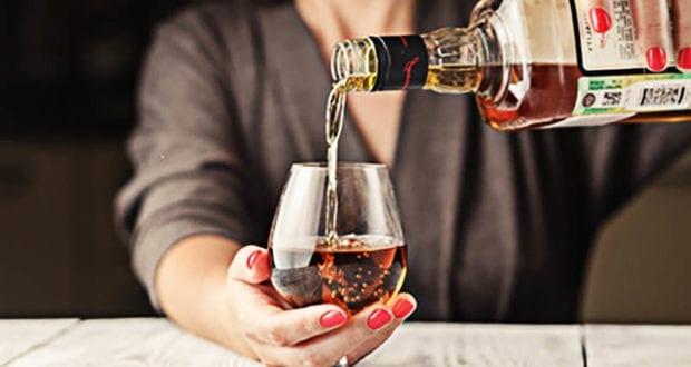 Frau schenkt sich Alkohol ein