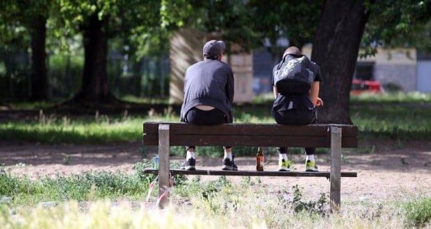 Jugendliche auf einer Parkbank mit Bier