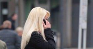 Blonde Frau mit Telefon