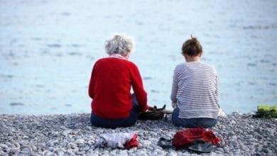 Alte und junge Frau sitzen am Strand dts